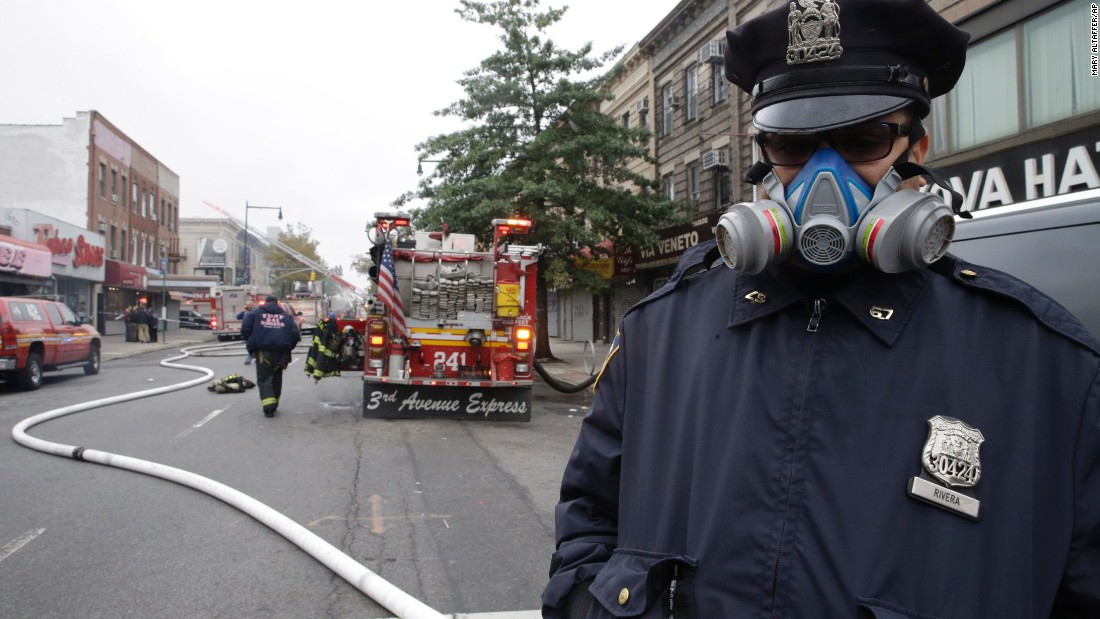 A police officer wears a mask while working near the scene.
