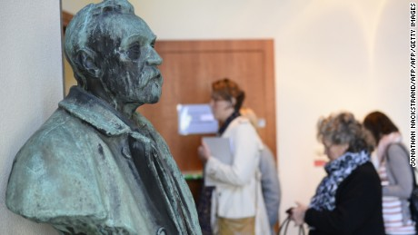 Journalists walk past a bust of Alfred Nobel as they arrive to attend a press conference of the Nobel Committee to announce the winner of the 2015 Nobel Medicine Prize on October 5, 2015 at the Karolinska Institutet in Stockholm, Sweden.    AFP PHOTO / JONATHAN NACKSTRAND        (Photo credit should read JONATHAN NACKSTRAND/AFP/Getty Images)