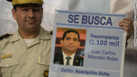 National Civil Police Director Walter Vasquez  shows a wanted poster with the picture of Juan Carlos Monzon, alleged leader of a customs corruption network, during a press conference at the Police headquarters in Guatemala City on June 20, 2015. Guatemalan Vice President Roxana Baldetti resigned on May 8 amid a corruption scandal in the customs system in which her former  private secretary Juan Carlos Monzon was allegedly involved. AFP PHOTO / Johan ORDONEZ .        (Photo credit should read JOHAN ORDONEZ/AFP/Getty Images)