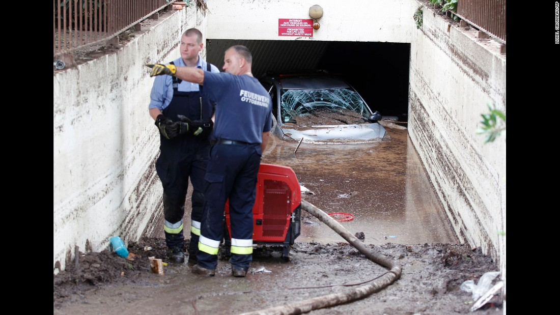 "Rescue workers pump water out of a garage in Mandelieu-la-Napoule, France, on Monday, October 5. Rainfall on an ""exceptional scale"" set off flash floods that have wreaked havoc along France's southeastern coast. At least 19 people are dead."