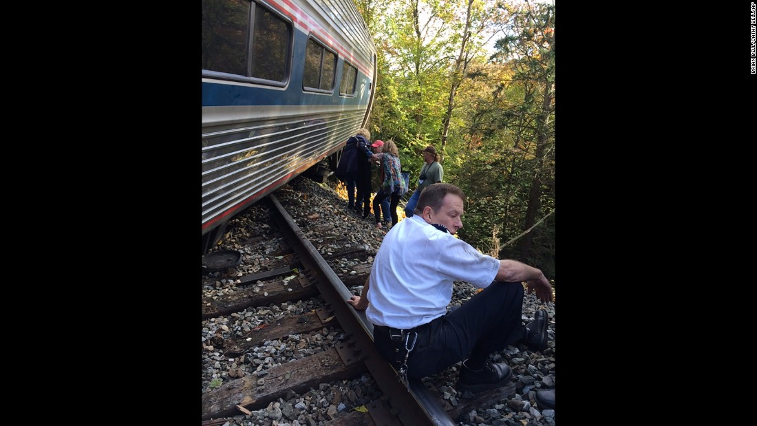 One of the train crew members sits next to one of the derailed cars shortly after the accident.