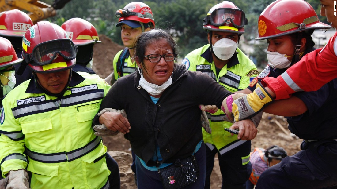 Rescue workers help a woman after she identified two family members at the site of the landslide on Saturday, October 3.