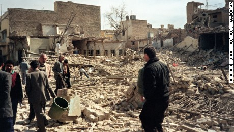 Iraqi civil defense workers and civilians look at destroyed houses after an allied bombing raid on a Baghdad street in February 1991.