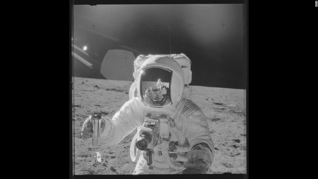 Astronaut Alan Bean holds a sample of lunar soil during Apollo 12. Pete Conrad's reflection can be seen in Bean's visor as he takes the photo.