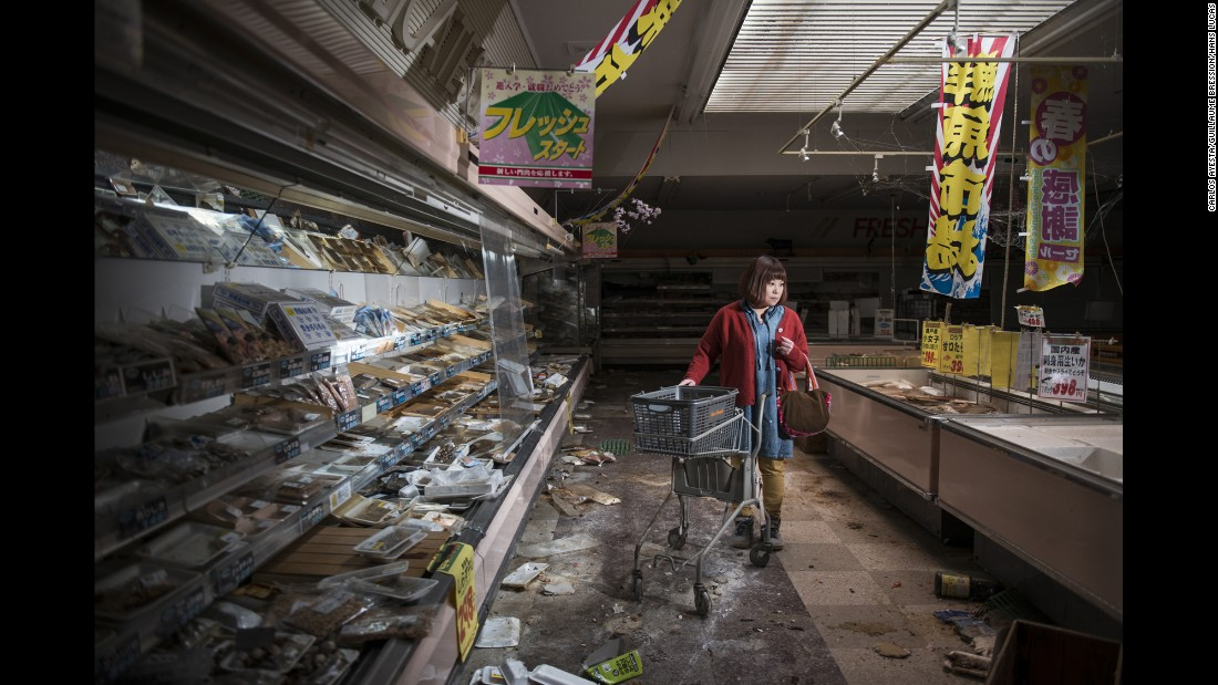 Following the 2011 Fukushima meltdown, photographers and documentarians Carlos Ayesta and Guillaume Bression made multiple trips to the no-go zone, photographing former residents of the region nearly five years later. Here, Midori Ito is staged in an abandoned supermarket in the prohibited city of Namie. Just after the disaster, Midori Ito evacuated to Minami Aizu for fear of health risks associated with radioactivity.