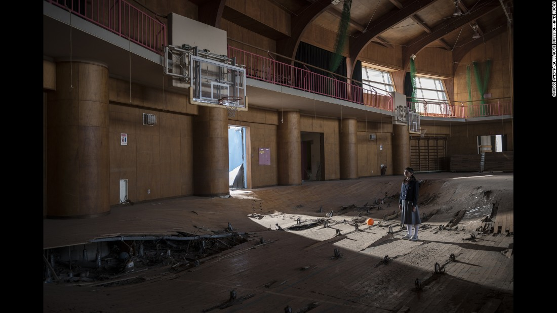 Kanoko Sato stands in a destroyed gym in Ukedo.