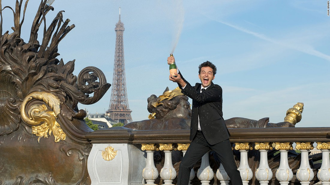 Stop with all the Paris cliches, says comedian Olivier Giraud, pictured here standing in front of the Eiffel Tower. With a bottle of Champagne.