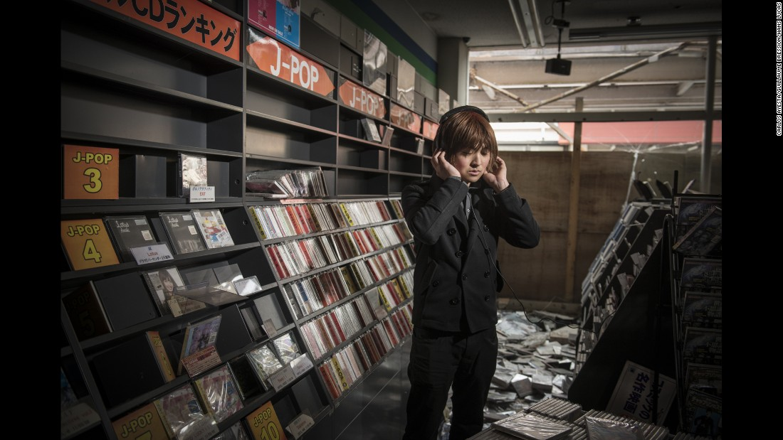 Noboru Eda stands in an abandoned music store in Namie.