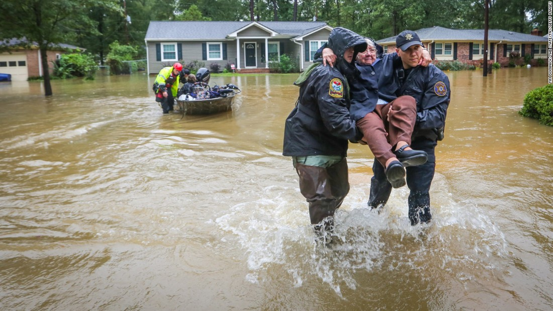"Department of Natural Resources Officer Brett Irvin and Lexington County Deputy Dan Rusinyak carry June Loch to dry land after she was rescued from her home on Monday, October 5, in the St. Andrews area of Columbia, South Carolina. The state experienced <a href=""http://www.cnn.com/2015/10/03/us/gallery/east-coast-flooding/index.html"" target=""_blank"">record rainfall</a> over the weekend, forcing hundreds of evacuations and rescues."