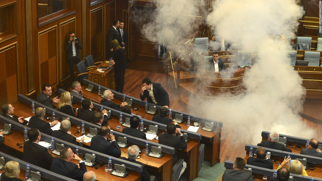 Opposition lawmakers throw tear gas during a session of Kosovo's parliament on Thursday, October 8. The protest was against agreements that had been reached during the EU-brokered dialogue with Serbia.