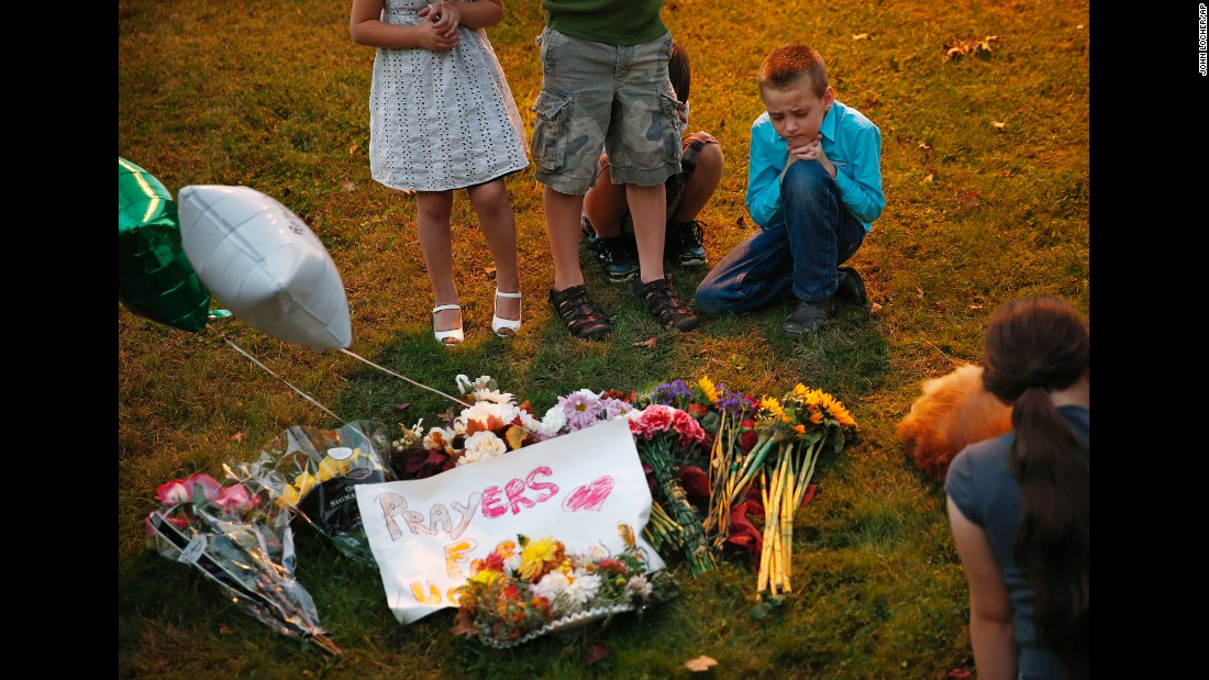"Ethan Hurley, 7, top right, prays with a church group at a makeshift <a href=""http://www.cnn.com/2015/10/02/us/oregon-umpqua-community-college-shooting/"" target=""_blank"">memorial near Snyder Hall</a> at Umpqua Community College on Sunday, October 4, in Roseburg, Oregon. The man who gunned down nine people and wounded several others on Thursday, October 1, took his own life at the scene."