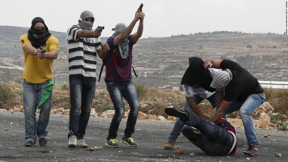 Members of the Israeli security forces detain a Palestinian stone thrower and aim their weapons at fellow protesters during clashes on the outskirts of the West Bank city of Ramallah, on Wednesday, October 7.