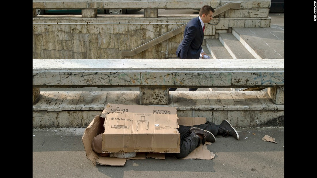 A pedestrian exits a subway station as a homeless man sleeps covered in cardboard packaging outside the main railway station in Bucharest, Romania, on Wednesday, October 7.