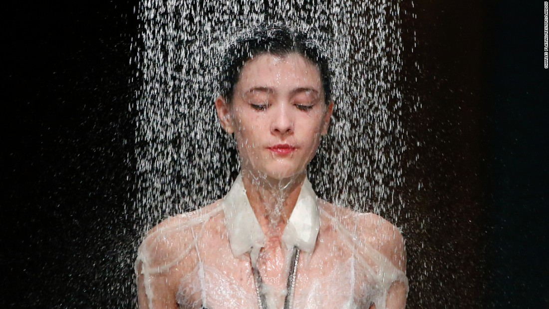 Water falls on a model as she presents a creation by designer Hussein Chalayan during the Fashion Week in Paris on Friday, October 2. <br />