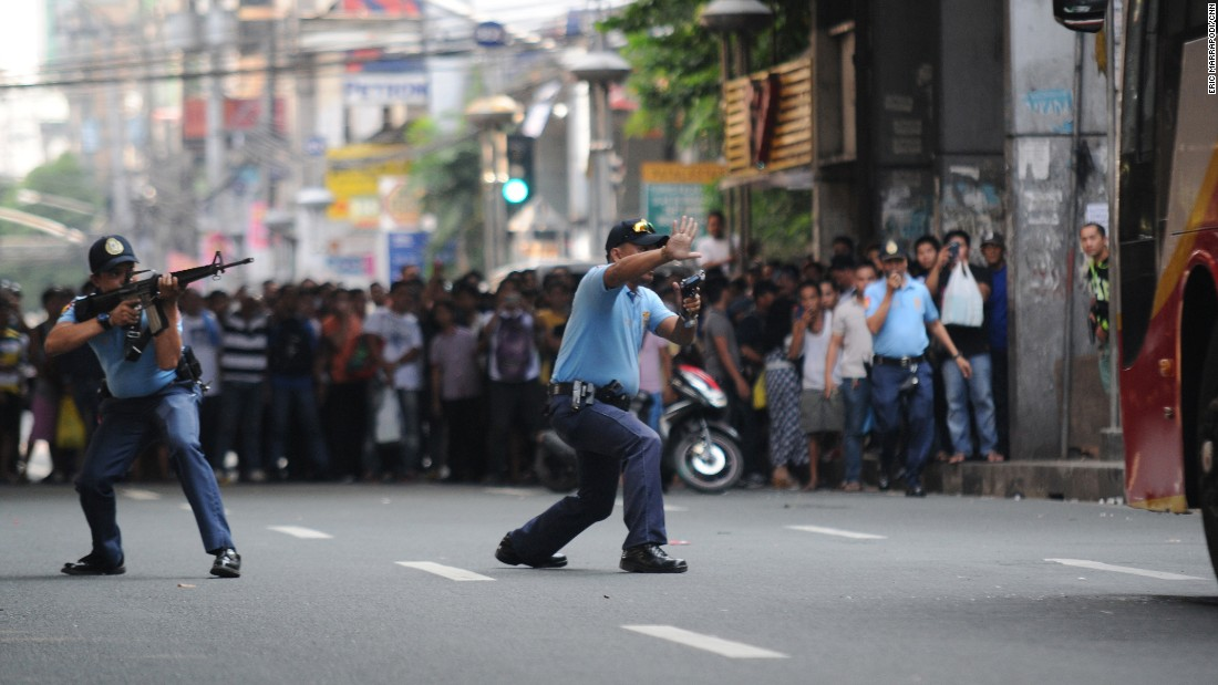 Filipino policemen aim their guns toward a hostage-taker, not shown, inside a passenger bus as a crowd watches in Manila, Philippines, on Thursday, October 8. The hostage-taker later died at the hospital after being shot by police.