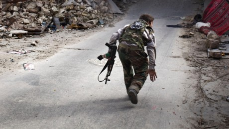 A Syrian rebel crosses a street while trying to dodge sniper fire in the old city of Aleppo in northern Syria on March 11, 2013.