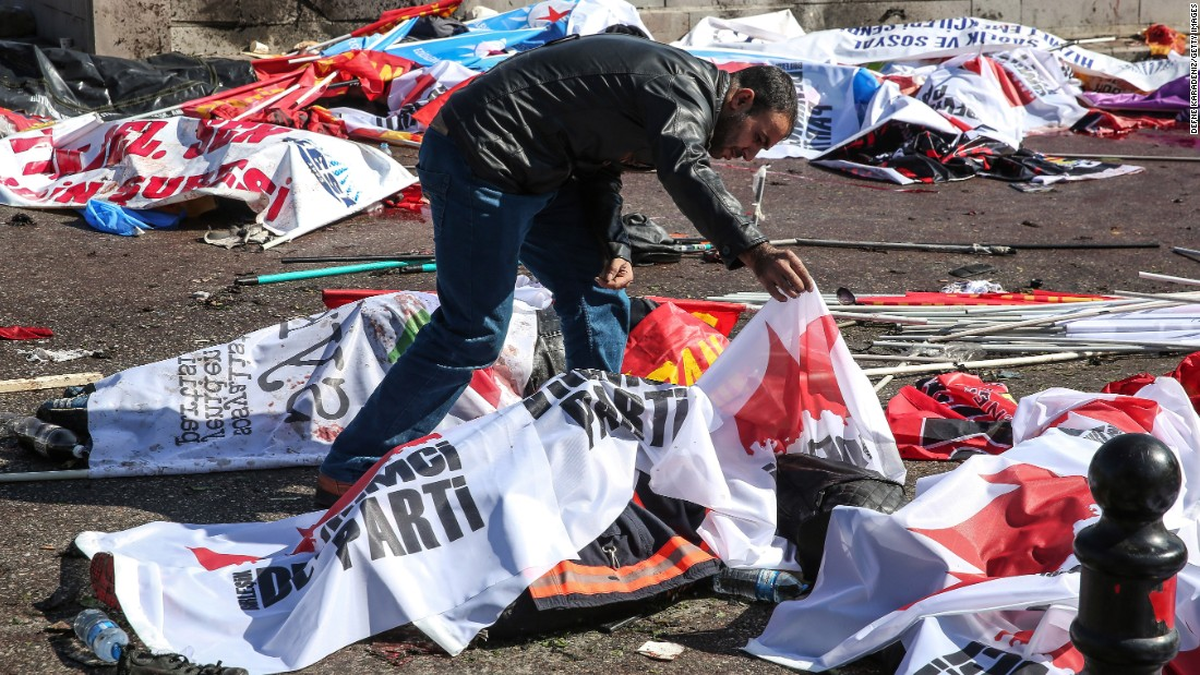A man looks at a body at the site of the explosion.