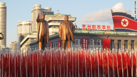 North Korean soldiers march below statues of North Korea's founding president Kim Il-sung and his son Kim Jong-il.
