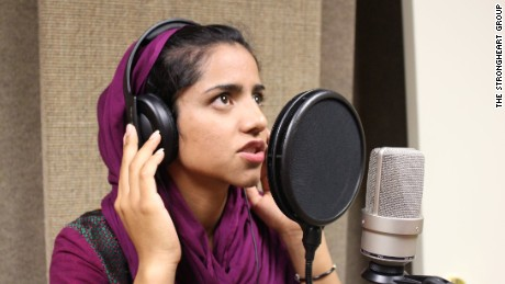 Sonita Alizadeh raps into a microphone at a music studio on her campus at Wasatch Academy.