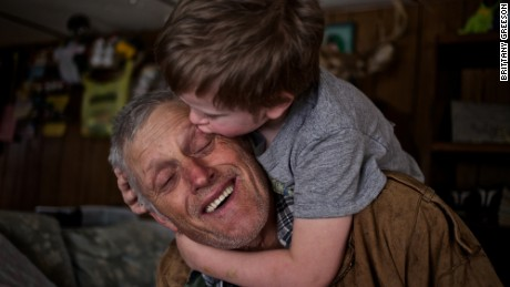 "Skylor Cox, 3, jumps on his father's back to give him ""little kissies"" at their home in Fordsville, Ky., on February 15, 2014.