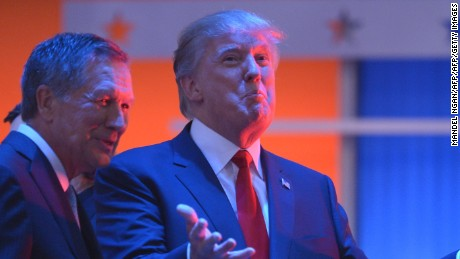 Real estate tycoon Donald Trump (R) confers with Ohio Governor John Kasich (L) during a break in the  Republican presidential primary debate on August 6, 2015 at the Quicken Loans Arena in Cleveland, Ohio.  AFP PHOTO / MANDEL NGAN        (Photo credit should read MANDEL NGAN/AFP/Getty Images)
