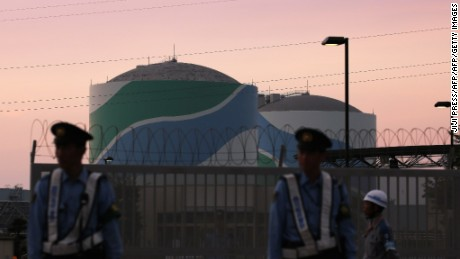 Nuclear reactor buildings of the Kyushu Electric Power Sendai nuclear power plant are seen behind police officers standing guard in the twilight in Satsumasendai in Kagoshima prefecture, on Japan's southern island of Kyushu on August 11, 2015.