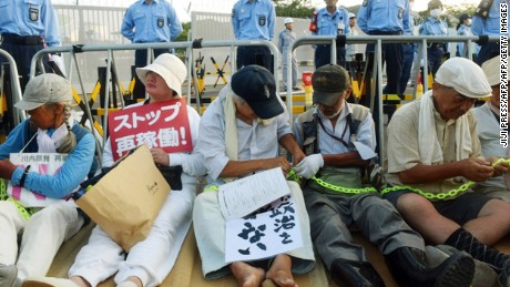 People stage a sit-in rally outside the gates of the Kyushu Electric Power Sendai nuclear power plant on August 11, 2015, as the first reactor was brought back online. Restarts are part of a raft of unpopular policies that are being pushed by Abe's government.