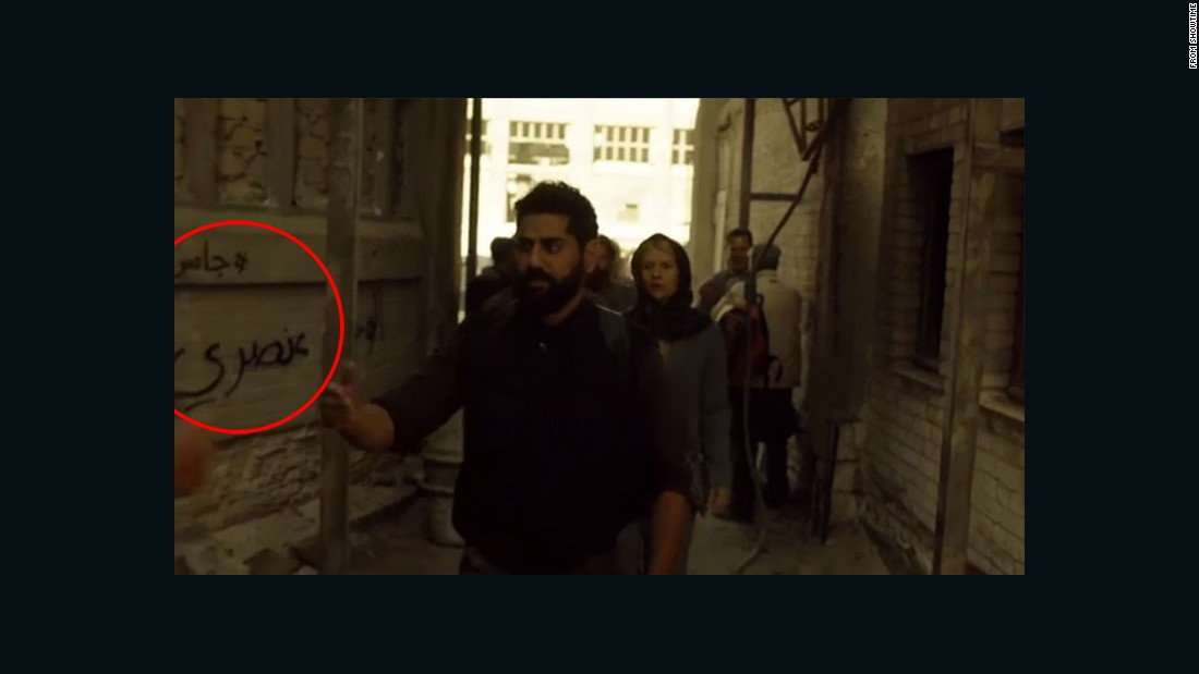 "Danes as Carrie Mathison walking through a fictional Syrian refugee camp past the graffiti slogan: ""Homeland is racist."""