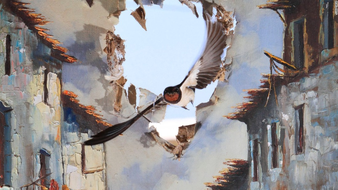 Impressions winner - 'Life comes to art', by Juan Tapia, Spain. <br /><br />Every summer, barn swallows return to nest in an old storehouse on Juan's farm. So he hung a ripped oil painting before a shattered window through which he knew the birds entered. Eight hours later, using remote control, he caught this moment, as though the bird had punched in from another world.