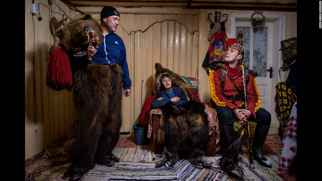 "Catalin Apetroaie chats with a young bear and the ""bear tamer"" seated on his porch. They and the rest of the troupe have just finished performing for a family and are taking a rest before they continue on to the homes of other patrons."
