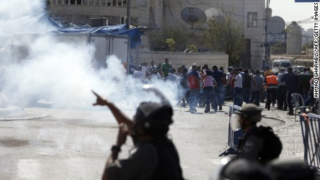 "Israeli security forces fire tear gas canisters and stun grenades towards Palestinian protesters after the Friday prayers in the Ras al-Amud neighbourhood in east Jerusalem, on October 16, 2015. Palestinians called for a ""Friday of revolution"" against Israel, and Jerusalem police barred men under 40 from attending the main weekly prayers at the flashpoint Al-Aqsa mosque, seeking to keep young protesters away."