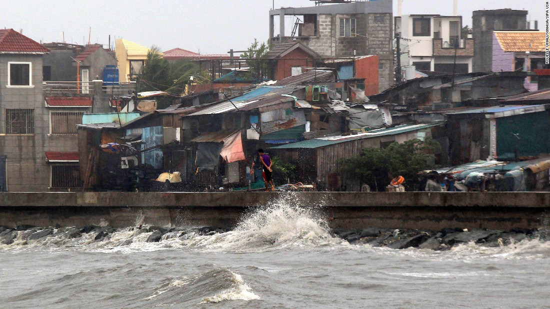 A man walks on a breakwater of Manila Bay in strong wind from Typhoon Koppu in Navotas,  Philippines, on Sunday October 18. Koppu is forecast to lumber over the country's main island of Luzon at an excruciatingly slow pace and dump huge amounts of rain on the rugged terrain, setting off floods and landslides.