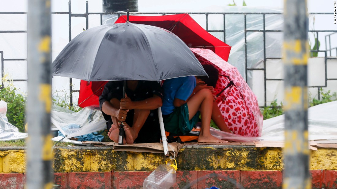 Residents huddle under umbrellas as strong winds and slight rain are brought by Typhoon Koppu on October 18 in Manila.