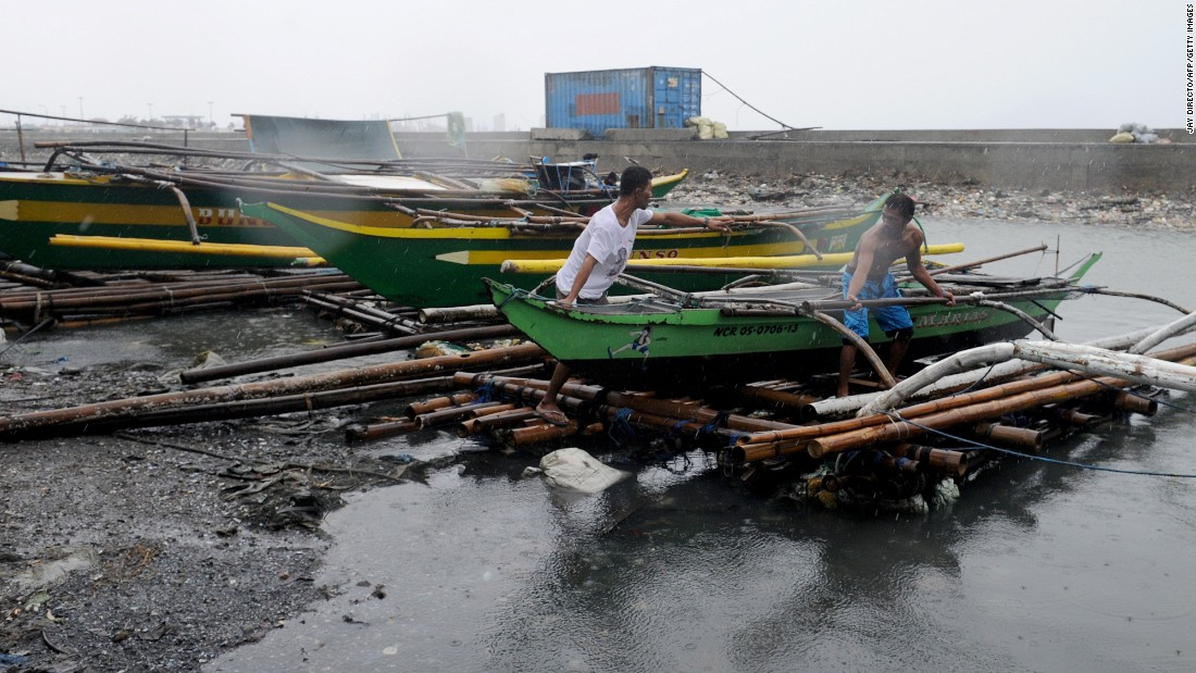Fishermen move outrigger boats to higher ground along the coastal area of Manila Bay on October 18.  The coast guard banned sailing.