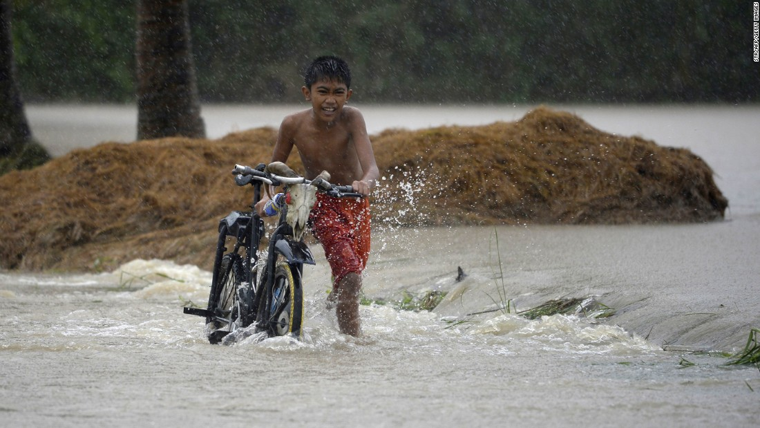 A child pushes his bicycle as he crosses a flooded street in Ineangan after the Magat River swelled.