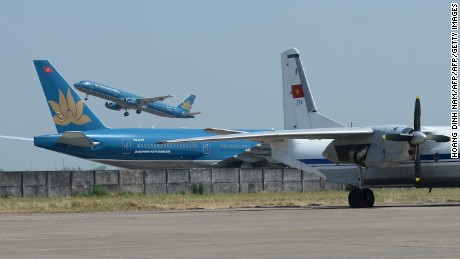 "Vietnam Airlines' planes (L) are seen passing a Vietnam Air Force's grounded Russian-made AN-26 aircraft which was used along with other types of aircrafts at finding the missing Malaysia Airlines plane at Tan Son Nhat airport in Ho Chi Minh city on March 15, 2014.  A Malaysian jet that vanished a week ago appears to have changed course and continued flying for hours, a senior Malaysian military official said, citing radar data indicating a ""skilled, competent"" pilot was at the controls.    AFP PHOTO/HOANG DINH NAM        (Photo credit should read HOANG DINH NAM/AFP/Getty Images)"