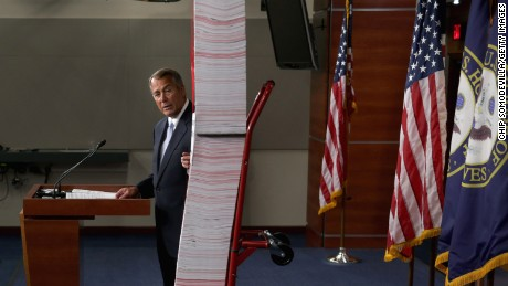 Speaker of the House John Boehner (R-OH) stands next to a printed version of the Patient Protection and Affordable Care Act, or Obamacare, during a news conference on Capitol Hill May 16, 2013 in Washington, DC.