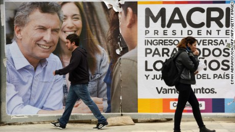 People walk past political propaganda of Buenos Aires Major and presidential candidate for Cambiemos party Mauricio Macri in Buenos Aires on October 19, 2015. General elections will be held next October 25 in Argentina. AFP PHOTO/Eitan Abramovich        (Photo credit should read EITAN ABRAMOVICH/AFP/Getty Images)