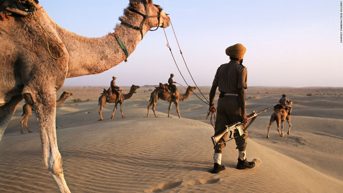 "Here, India's Camel Corps patrol desert near the Pakistan border, in 1996.<br /><br />""McCurry's India is, above all, a world of paradox,"" explains Dalrymple.<br /><br />""It is where border guards ride camels through the timeless deserts of the Thar, carrying the latest in modern M-16 high-velocity assault rifles.""<br />"