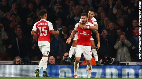 LONDON, ENGLAND - OCTOBER 20:  Olivier Giroud of Arsenal (C) celebrates with Alex Oxlade-Chamberlain (15) and Alexis Sanchez as he scores their first goal during the UEFA Champions League Group F match between Arsenal FC and FC Bayern Munchen at Emirates Stadium on October 20, 2015 in London, United Kingdom.  (Photo by Paul Gilham/Getty Images)