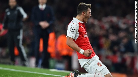 Arsenal's German midfielder Mesut Ozil (R) celebrates scoring his team's second goal during the UEFA Champions League football match between Arsenal and Bayern Munich at the Emirates Stadium in London, on October 20, 2015.  Arsenal won the match 2-0.  AFP PHOTO / BEN STANSALL        (Photo credit should read BEN STANSALL/AFP/Getty Images)