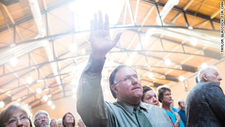 A man raises his hand in praise during the National Anthem before the Iowa Faith and Freedom Coalition annual banquet and presidential forum  Saturday Sept. 19, 2015 in Des Moines, Iowa. (Taylor Glascock for CNN)