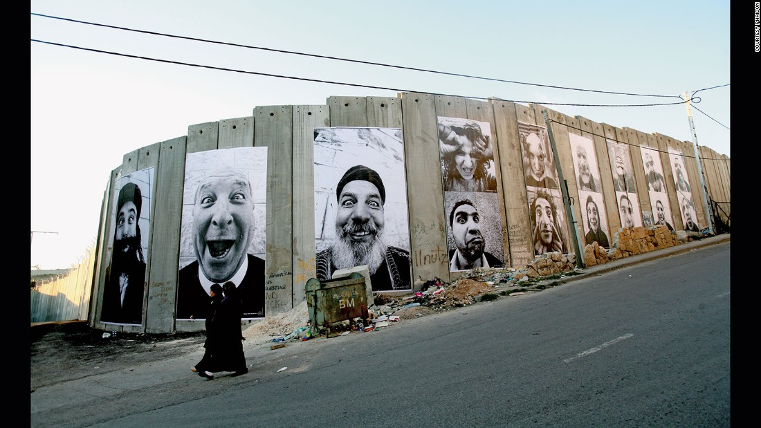 JR and his friend Marco went to the Middle East in 2005 and captured a series of photographs of Palestinian and Israeli people they met on their travels. In 2007, JR paired these photos face to face and plastered the images on walls in cities across Israel and the Palestinian territories. This photo was taken in the West Bank town of Bethlehem.