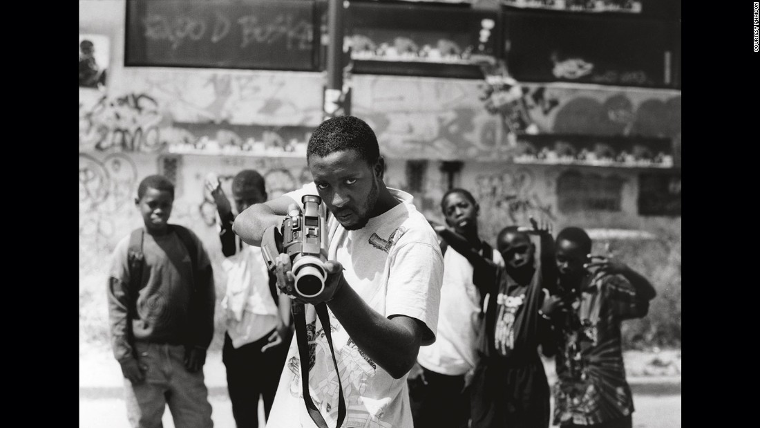 "JR took this photo of young French-Malian man Ladj Ly's as part of his ""Portrait of a Generation"" project. At first glance the man looks as though he's pointing a gun, but it is in fact a camera -- the photo challenges the ideas of clichés in visual culture. <br />"