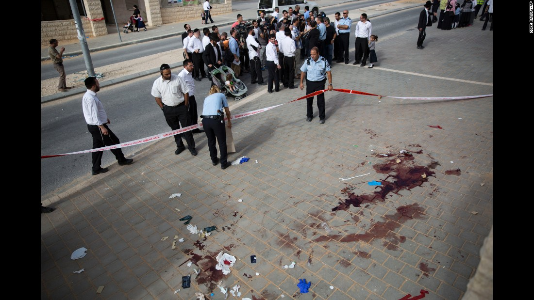Israeli police inspect the scene of a stabbing attack in Beit Shemesh, Israel, on Thursday, October 22. Two Palestinian men armed with knives tried to board a bus carrying children but were forced back by people inside the vehicle, police said. The two men were shot by police after they stabbed an Israeli man at a bus stop.