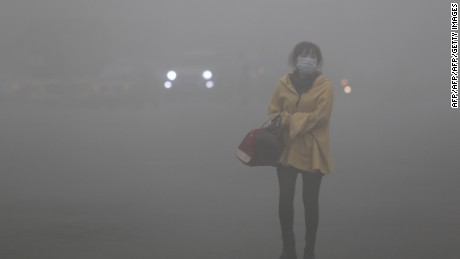 A woman wearing a face mask walks in heavy smog in Harbin, northeast China's Heilongjiang province, on October 21, 2013. Choking clouds of pollution blanketed Harbin, a Chinese city famed for its annual ice festival on October 21, reports said, cutting visibility to 10 metres (33 feet) and underscoring the nation's environmental challenges.   CHINA OUT     AFP PHOTO        (Photo credit should read STR/AFP/Getty Images)