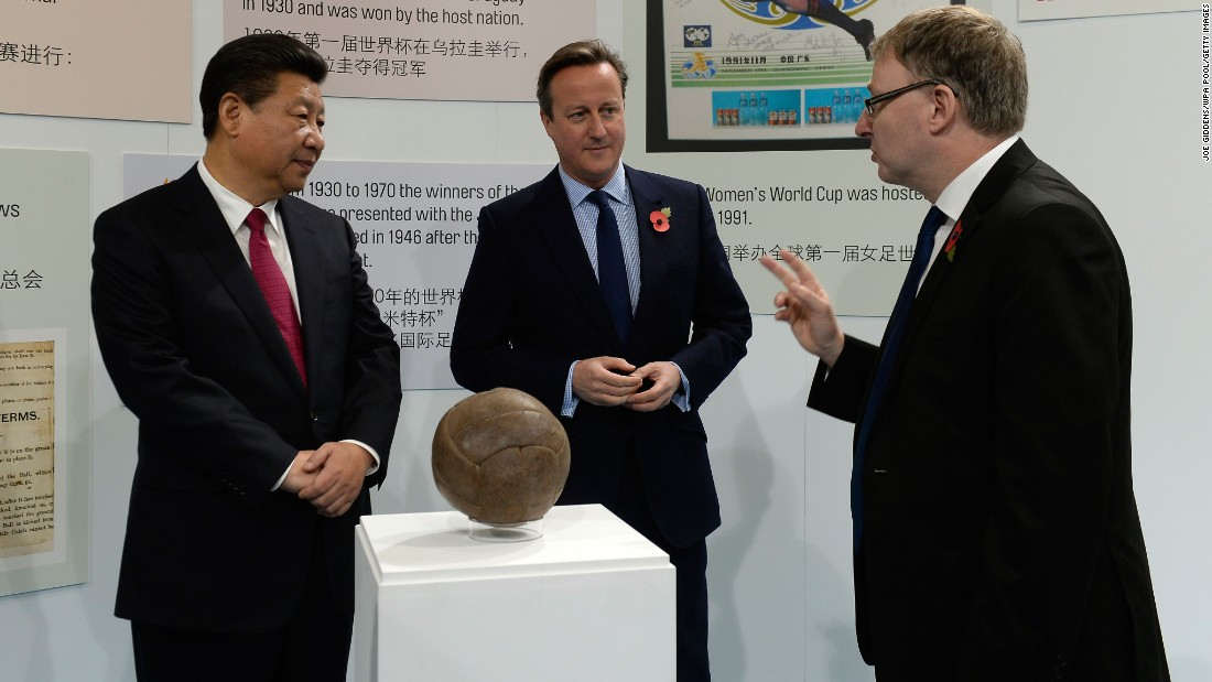 Xi and Cameron view the ball used in the first World Cup final during a visit to the City Football Academy in Manchester on October 23.