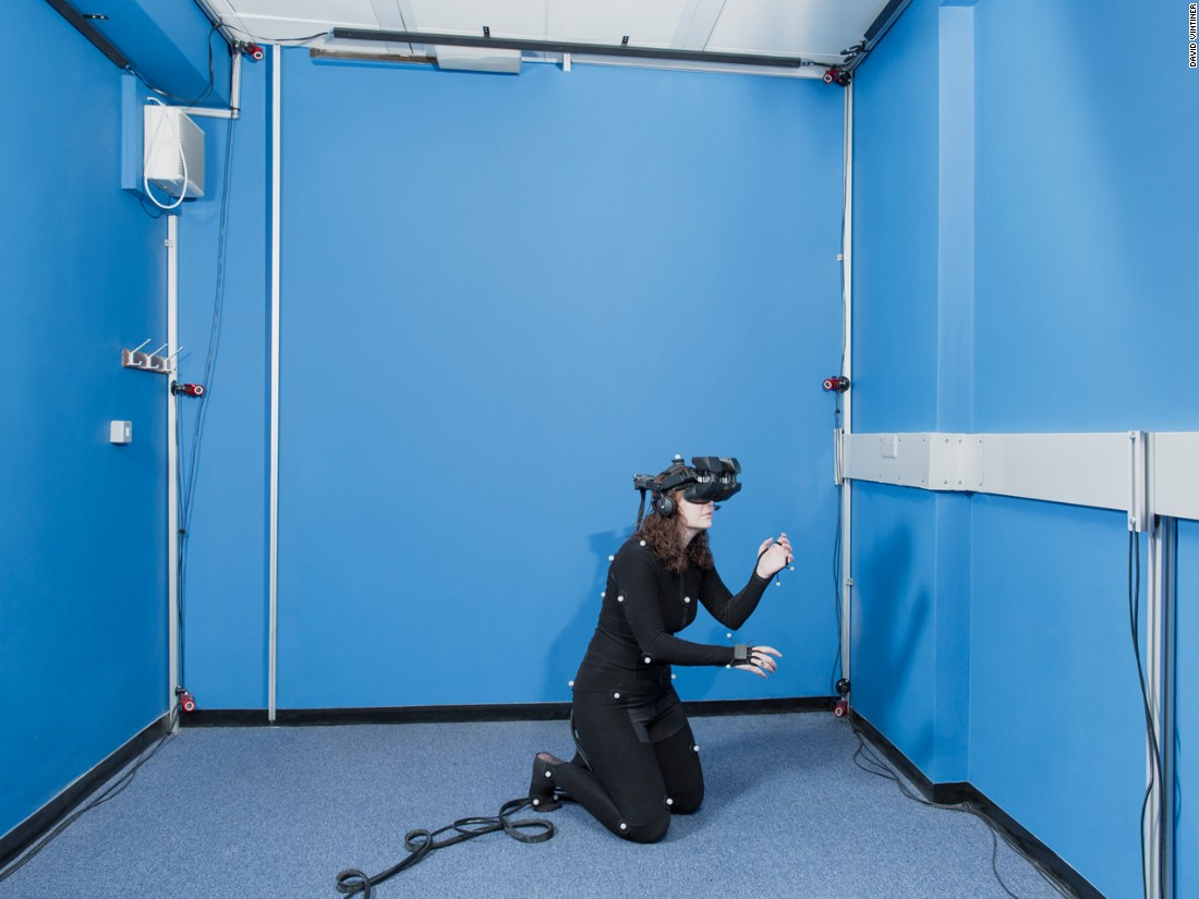 Psychologist/neuroscientist Dr. Caroline Falconer of the University of Nottingham is developing ways to use virtual reality to treat depression. In the photo, Falconer demonstrates a head-mounted, high-definition, 3-D display with full-body tracking. Patients use this gear to spatially substitute their own bodies with an avatar. Falconer is shown reaching out to comfort a crying, virtual child in a computer program aimed at cultivating self-compassion.
