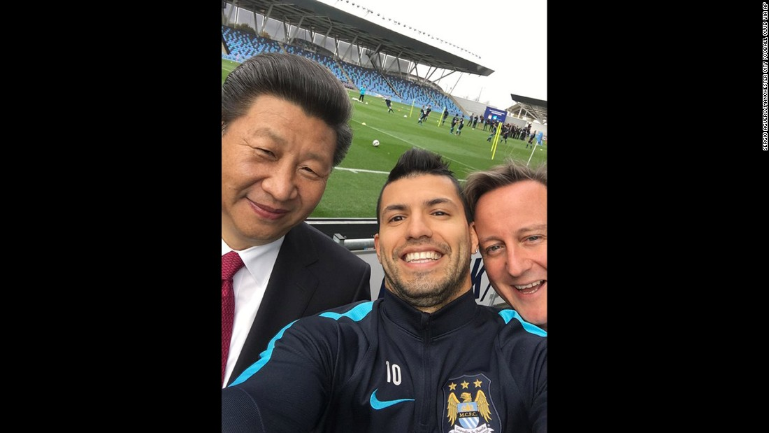 Manchester City soccer player Sergio Aguero takes a selfie with Xi and Cameron during a visit to the soccer club's practice session on October 23.