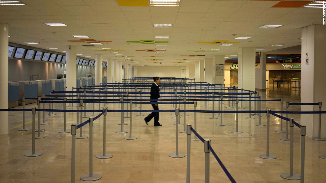 An airline employee walks around the empty airport in Puerto Vallarta, where all flights were canceled on October 23.